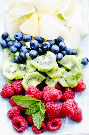 kiwis: Fresh fruit (blueberries, kiwis, raspberries) with mint leaves LANG_EVOIMAGES