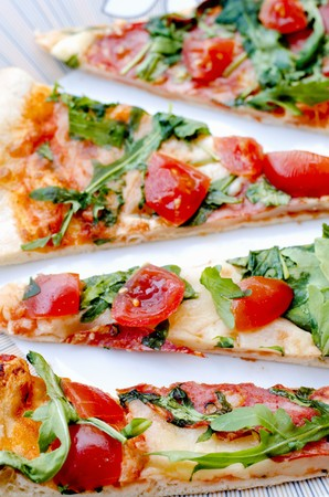 arugola: Slices of pizza topped with fresh rocket and cherry tomatoes