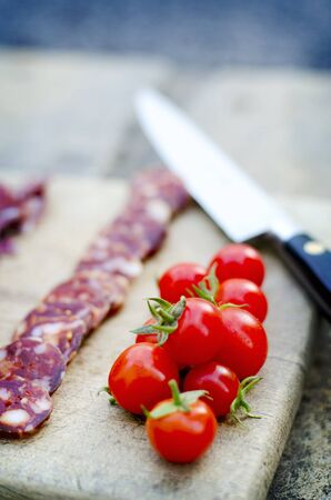 dry sausage: Chorizo slices on a wooden board with cherry tomatoes
