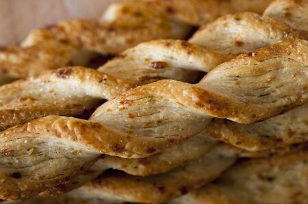 breadstick: A stack of Parmesan breadsticks on a wooden board