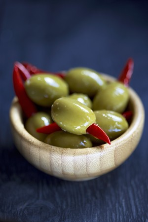 greenness: Green olives, stuffed with chilli peppers, in a wooden dish