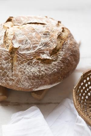 canasta de pan: Una hogaza de pan r�stico junto a una cesta de pan