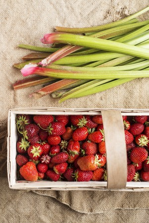 rheum: Strawberries in a wooden basket next to rhubarb
