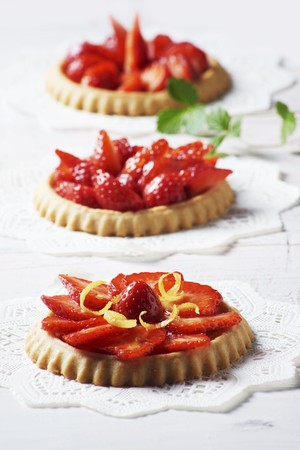 doiley: Three strawberry tartlets with lemon zest on doilies LANG_EVOIMAGES