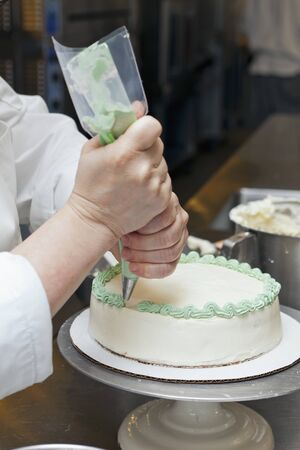 provenance: A chef icing a cake LANG_EVOIMAGES