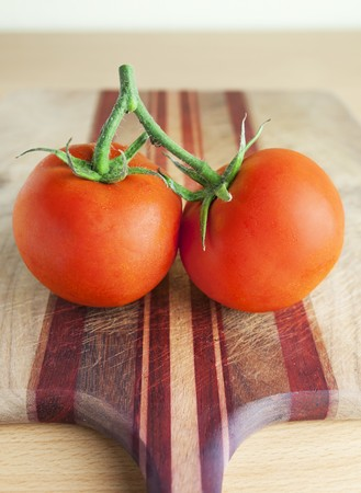 chopping board: Two vine tomatoes on a chopping board LANG_EVOIMAGES