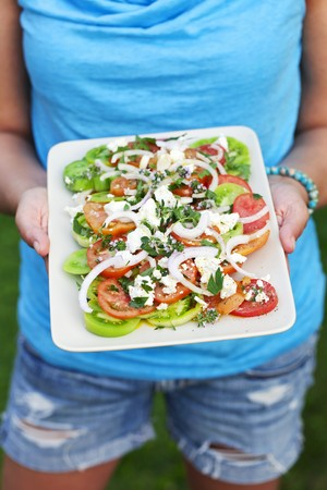 serve one person: A woman holding a plate of Greek salad LANG_EVOIMAGES