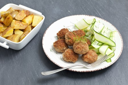 Meatballs served with a courgette salad and roast potatoes LANG_EVOIMAGES