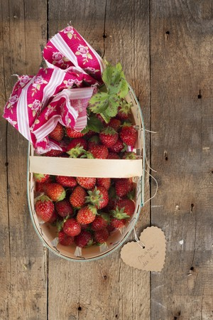 fragaria: Strawberries in a wooden basket with a heart-shaped label