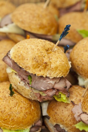 food: Roast beef sandwiches fastened with cocktail sticks