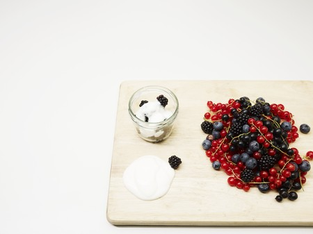 Fresh berries on a wooden board and yogurt with blackberries LANG_EVOIMAGES