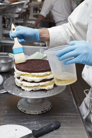 provenance: A chef brushing oil onto a layer cake LANG_EVOIMAGES