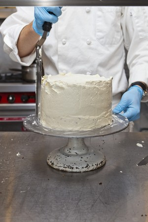 butter icing: A confectioner decorating a cake