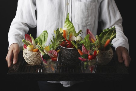 crudite: A man serving a tray of raw vegetables LANG_EVOIMAGES