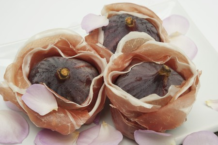 casings: Prosciutto Wrapped Figs on White Platter