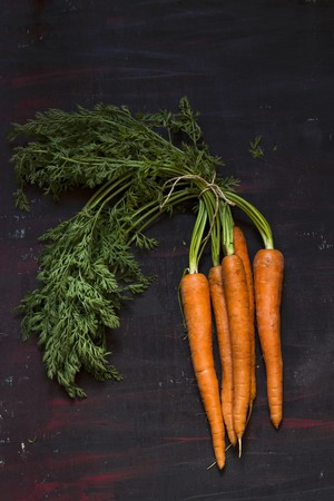 bunched: A bunch of fresh carrots with leaves on dark surface LANG_EVOIMAGES