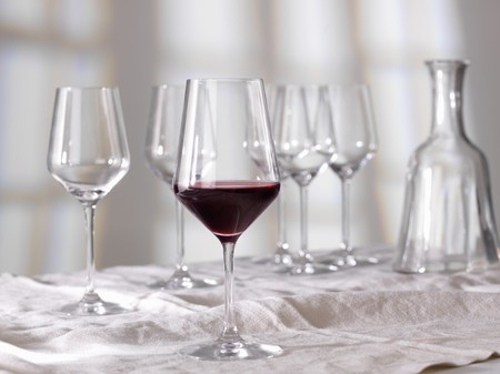 half full: A half full glass of red wine in front of empty glasses and a caraffe