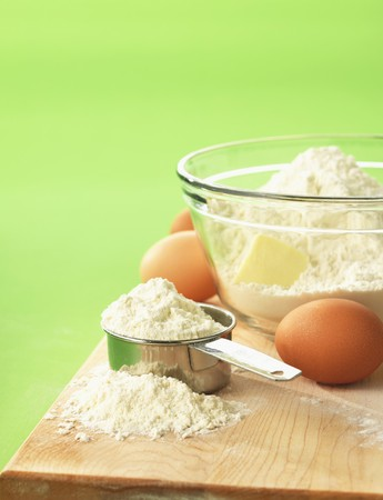 grain and cereal products: Flour, butter and eggs on a chopping board