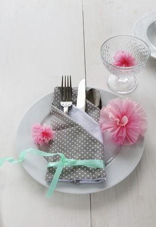 ides: A place setting with a napkin folded as a cutlery bag decorated with paper carnations