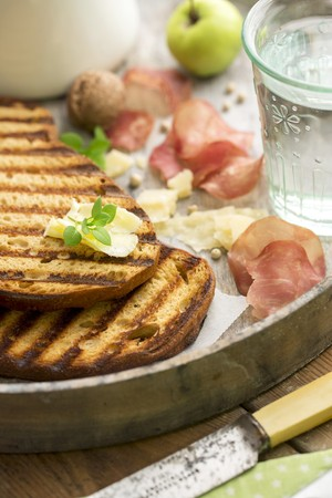 sel: Grilled bread with butter, Parmesan, ham crisps, walnuts, apple and a glass of water