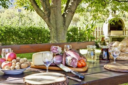 charcutería: Un plato de la cena suntuosa, una cesta de pan, frutas y frutos secos sobre una mesa de jardín LANG_EVOIMAGES