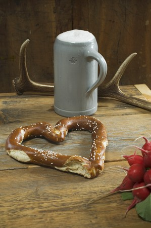 steins: A heart-shaped pretzel with radishes, a mug of beer and antlers on a wooden table