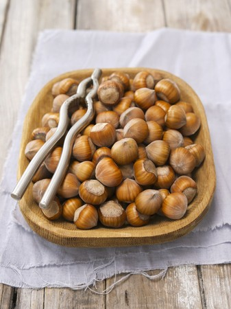 nutcracker: Hazelnuts in a wooden bowl with a nutcracker LANG_EVOIMAGES