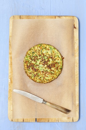 cocozelle: A courgette cake on baking paper with a knife
