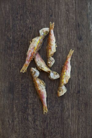 goatfish: Baby red mullet on a wooden surface LANG_EVOIMAGES