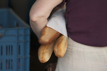 several breads: A woman holding three baguettes under her arm LANG_EVOIMAGES
