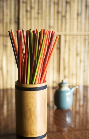 yellowish green: Colourful chopsticks in a bamboo container on a table in a restaurant