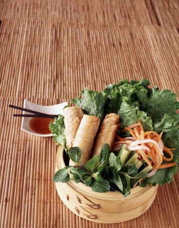 chilli sauce: Vegetarian spring rolls on a bed of lettuce with daikon radish and carrots served with sweet chilli sauce LANG_EVOIMAGES