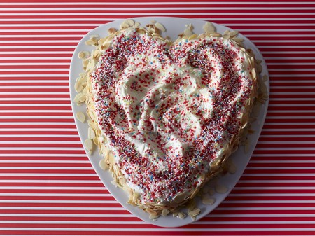 heartshaped: A heart-shaped cake decorated with colourful sprinkles and flaked almonds