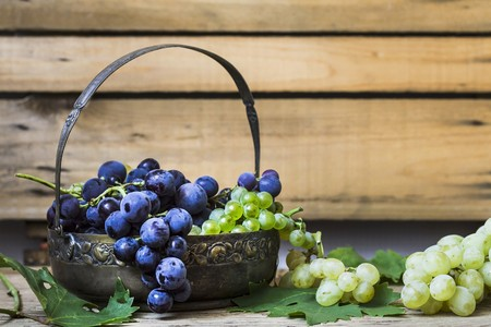 greenness: Red and green grapes in a metal basket