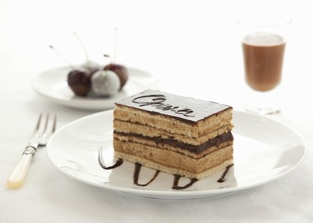 A slice of Opera Cake with cherries and a glass of chocolate liqueur in the background LANG_EVOIMAGES