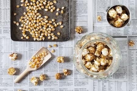 baking tray: A jar of caramel popcorn next to kernels on a baking tray