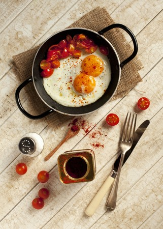 doubled: Two fried eggs and fried, chopped tomatoes sprinkled with paprika in a pan