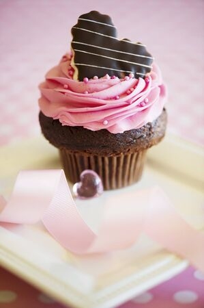 butter icing: A rose cupcake decorated with a chocolate heart LANG_EVOIMAGES