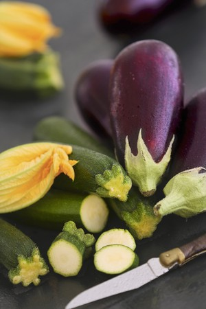 cocozelle: Aubergines and courgettes with flowers on a dark surface