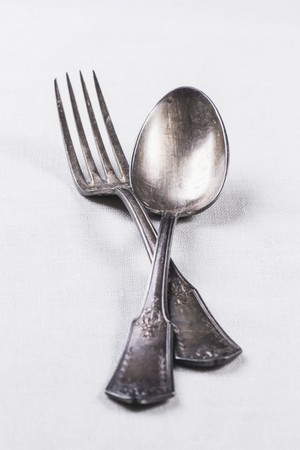 silver cutlery: Old silver cutlery on a white table cloth LANG_EVOIMAGES