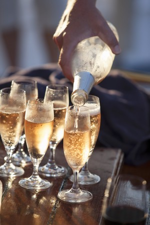 poured: Champagne being poured into six glasses LANG_EVOIMAGES