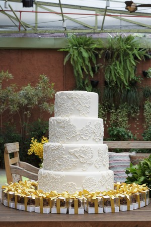 conservatories: A white, four tier wedding cake with mini boxes of pralines as gifts