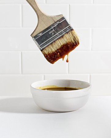 broiling: A brush being dipped in a bowl of barbecue sauce