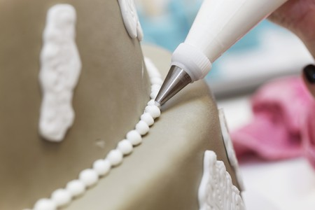butter icing: A fondant-covered cake being decoration with white icing LANG_EVOIMAGES