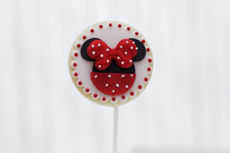 childrens food: A round biscuit lolly decorated with a red bow and dots LANG_EVOIMAGES