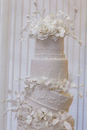 festoons: An artistically decorated wedding cake with elaborate flower decorations