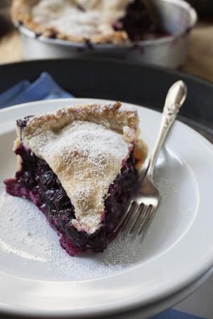 blueberry pie: Una rebanada de pastel de ar�ndanos espolvoreado con az�car glas en un plato