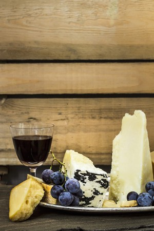 cheese platter: A cheese platter with grapes and a glass of red wine LANG_EVOIMAGES