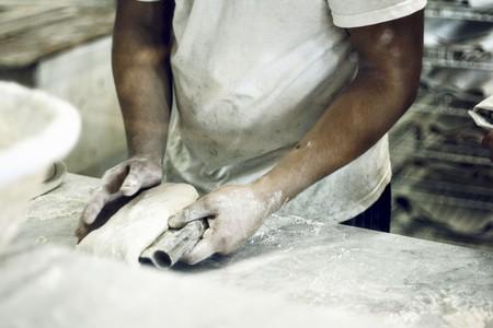 worktops: A baker kneading bread dough