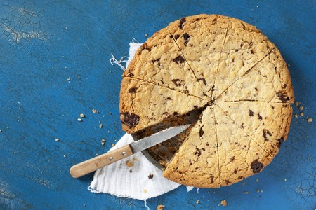 choco chips: A chocolate chip cookie cake in the tin with a piece missing LANG_EVOIMAGES